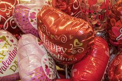 Big bunch of Valentine mylar heart shaped balloons with messages on them - taken from above stock photo