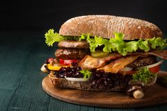 Big burger with bacon. Cutlet and mushrooms stock photography