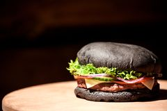 Big burger with black bun, cheese, onion, meat, tomato, cucumber and salad leaf placed on a wooden board. Big burger with black bun, cheese, onion, meat, tomato royalty free stock image