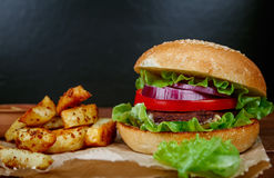 Big burger with fries on dark Royalty Free Stock Photography