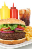 Big Burger with fries, soda, ketchup and mustard. Big juicy hamburger served with french fries, cola soda, ketchup and mustard. Fast Food Collection stock photo