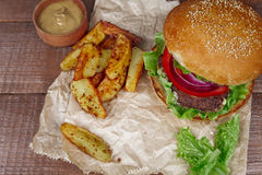 Big burger with fries on wooden Stock Images