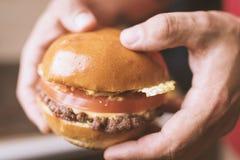 Big burger in man`s hands stock images