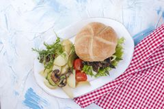 Big burger with salad and potatoes. Tasty dinner. Junk food. Flat lay. Copy space stock images