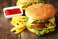 Big burgers on brown wooden background Stock Photos