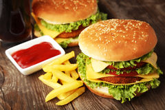 Big burgers on brown wooden background Stock Photography