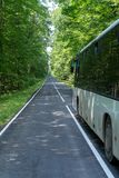 The big bus is moving along the forest road. royalty free stock photography