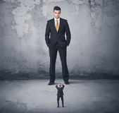 Big business bully looking at small coworker Royalty Free Stock Photo