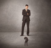 Big business man looking at small worker Stock Photo