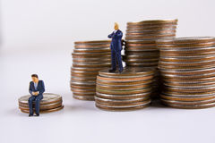Big Business vs. small business. Miniature business man sitting on stack of dimes with another business man standing on stack of quarters looking at him Stock Image