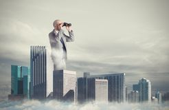 Businessman looks far for new business. Concept of new opportunities. Big businessman emerges from the skyscrapers with binoculars Royalty Free Stock Photography