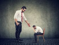 Big businessman giving a hand supporting a depressed desperate guy. Big businessman giving a hand supporting a depressed desperate little entrepreneur stock photography