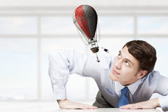 Big businessman peeping from under table Stock Images