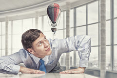 Big businessman peeping from under table Stock Photos