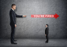 Big businessman poiting at red arrow with 'you're fired' Stock Photo