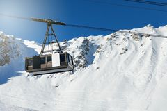 Big cable car on snowy winter mountain background. In ski resort stock images