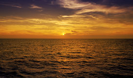 Big calm. Warm sunset on open ocean. The focus is on the sun stock photos