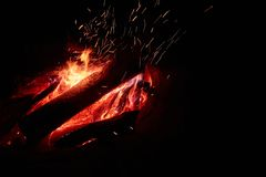 Big campfire at night with a lot of sparks. Isolated on the black background royalty free stock photo