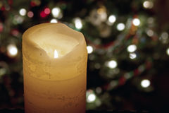 Big Candle and Christmas Lights. A large candle, glowing with is own flame before and soft-focused Christmas tree with white lights behind Royalty Free Stock Photo