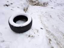 Big car tire on snow in winter. Very big old car tire in the snow in winter stock photos