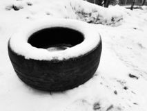 Big car tire on snow in winter. Very big old car tire in the snow in winter stock images