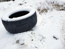 Big car tire on snow in winter. Very big old car tire in the snow in winter stock photography