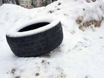 Big car tire on snow in winter. Very big old car tire in the snow in winter royalty free stock image