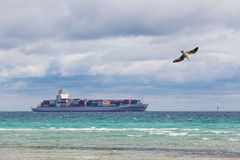 Big cargo ship filled with containers sailing across Mornington Royalty Free Stock Image