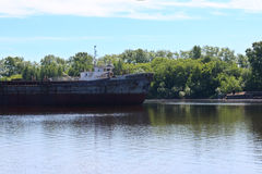 Big cargo ship are near shore with trees on river at summe. Big rusty cargo ship are near shore with trees on river at summer day Royalty Free Stock Photo
