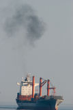 Big cargo ship on the sea with cloud of smoke. For illustration ecological problem Stock Image