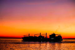 Big cargo ship silhouette leaving harbor. Royalty Free Stock Photography
