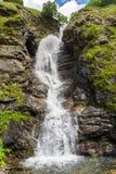 Big cascade waterfall. Beautiful big cascade sparkling  waterfall among high rocks with grass Royalty Free Stock Photography