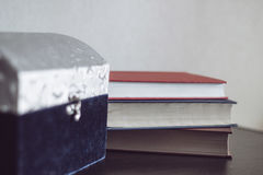 Big casket and books on a wood table. Big casket and three books on a wood table Royalty Free Stock Photos