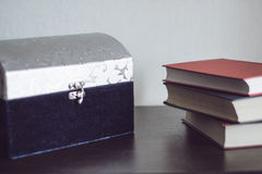 Big casket and books on a wood table. Big casket and three books on a wood table Stock Photo