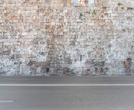 Big castle block stone wall and asphalt foreground texture. With road Royalty Free Stock Image