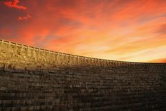 A big castle defensive wall in a sunset. We can imagine dragons and arrows flying over. The big wall protects who`s inside from enemies` attacks. The wall is stock photo
