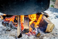 A big cauldron for cooking close-up over the fire at the nature during a hiking trip royalty free stock photos