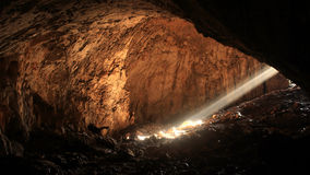 Big cave with bright sunbeam from entrance Stock Photo