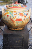 Big ceramic cauldron on a small iron stove. With colorful painting. cooking food on firewood. traditional Ukrainian cookware Royalty Free Stock Photography