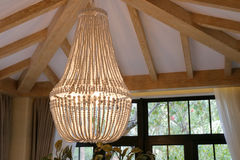 Big chandelier  under the wooden ceiling. Pendant lights in the room Stock Photos