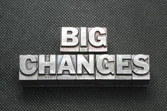Big changes bm. Big changes phrase made from metallic letterpress blocks on black perforated surface Stock Photo