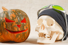 The big cheerful halloween pumpkin and skull. With sigarette from canvas background Royalty Free Stock Photo