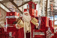 Big Cheerful Santa Claus doll Santa Claus and many red gift boxes with ribbons and on shiny background. Christmas Royalty Free Stock Images