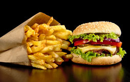 Big cheeseburger with french fries on black board. Big single cheeseburger with french fries on black wooden table Stock Photos