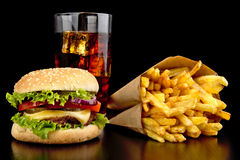Big cheeseburger with glass of cola and french fries on black de Stock Images
