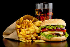 Big cheeseburger with glass of cola and french fries on black desk Royalty Free Stock Images