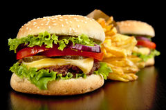 Big cheeseburgers with french fries on black board Royalty Free Stock Photo
