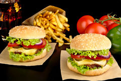 Big cheeseburgers on paper,french fries and glass of cola on black Stock Images