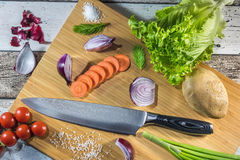 Big chef knife with healthy food - vegetables, onion, salad, potato placed on a cutting board with wood background top view Stock Photography