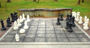 Big chess board with huge pieces in the park royalty free stock images